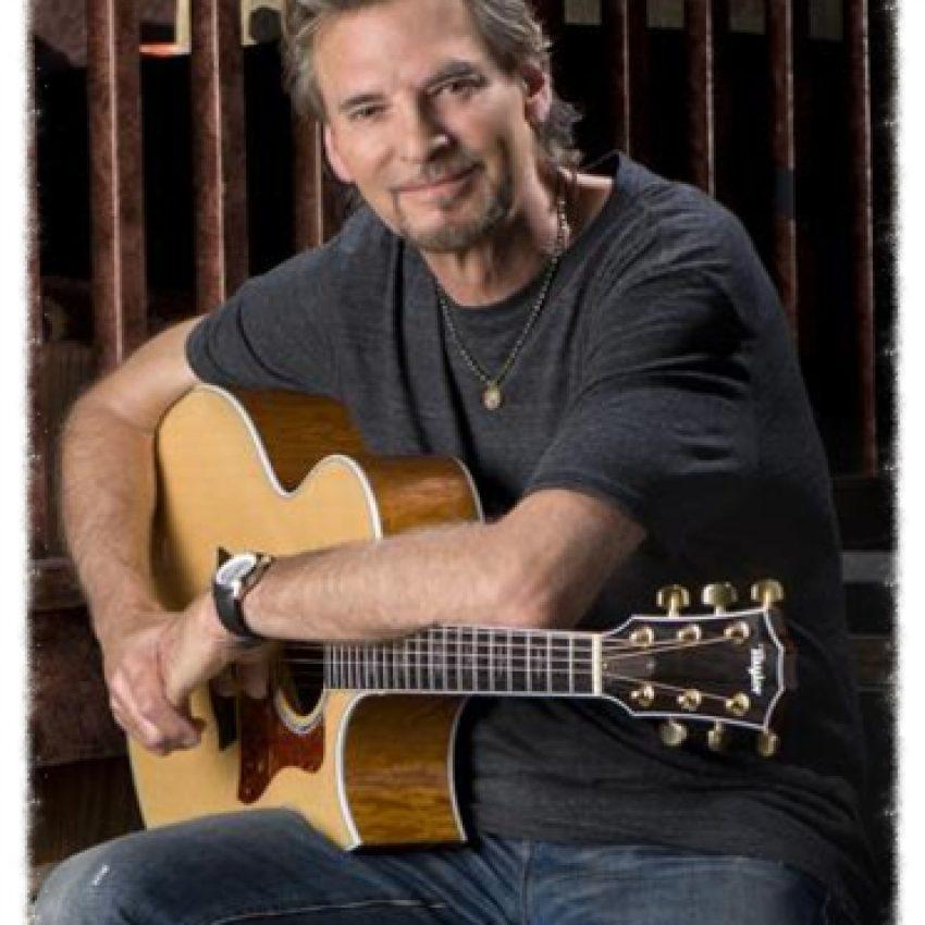 man wearing blue tshirt holding acoustic guitar on lap