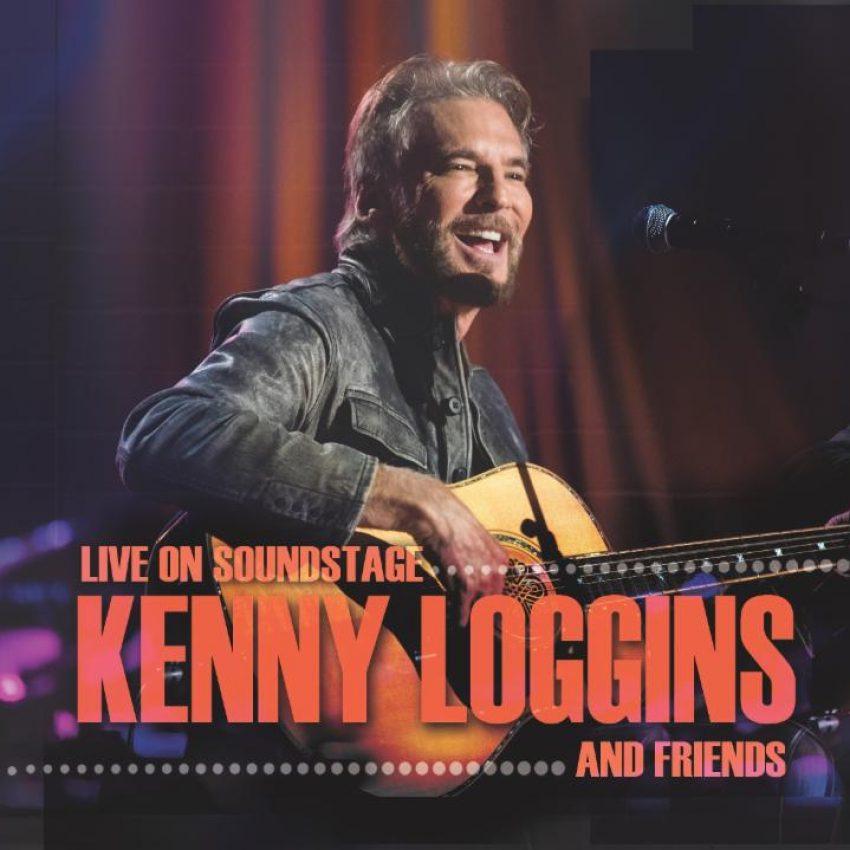 kenny loggins on stage holding acoustic guitar